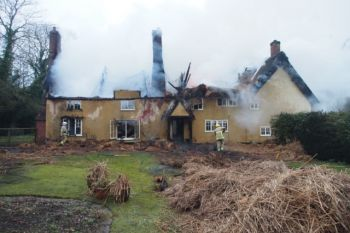 Firefighters tackling a thatch roof fire