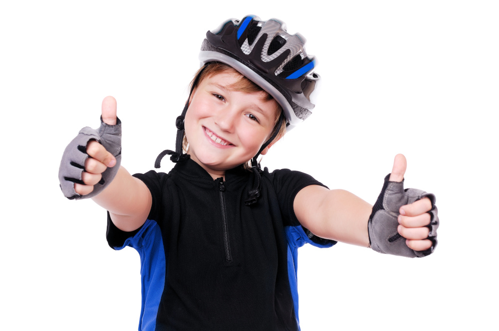 Child wearing a cycling helmet and giving a thumbs-up